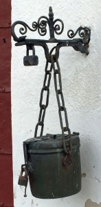 A  hanging, iron alms box.
