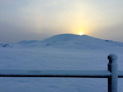 Sun peeking over the mound.